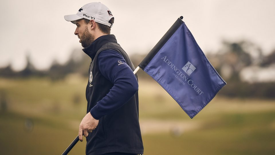 addington golfer holding crown golf flag